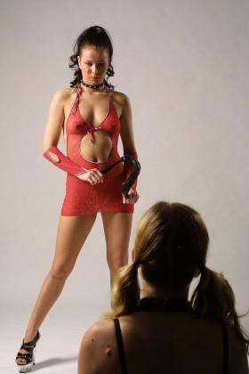 Brune dominatrice en tenue sexy avec un fouet