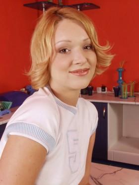 Blondinette sexy dans sa cuisine avec un top blanc