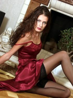 Barbara brune sexy en robe de soirée rouge et des bas et talons aiguilles
