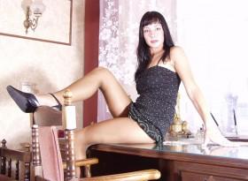 Lola brune salope assise sur le bureau robe relevée