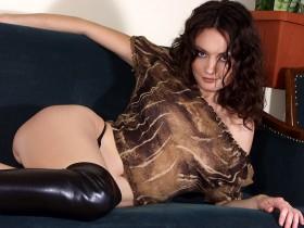 Kelly brune chaude pose sur son canapé en tenue sexy